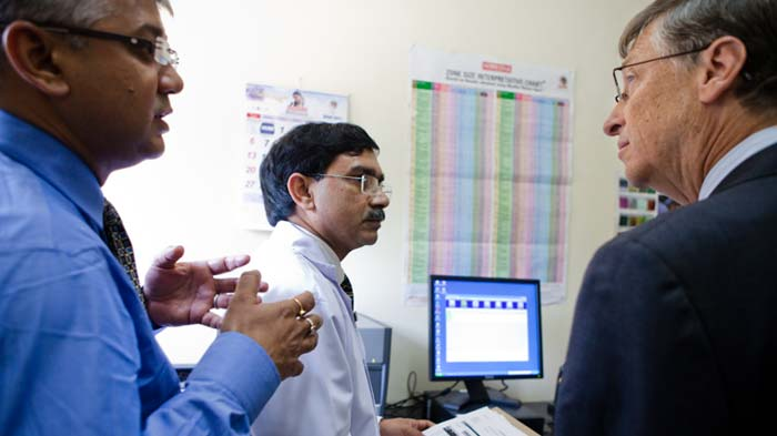 Bill Gates speaks with doctors in front of the GeneXpert diagnostic system at LRS Institute of Tuberculosis and Respiratory Diseases